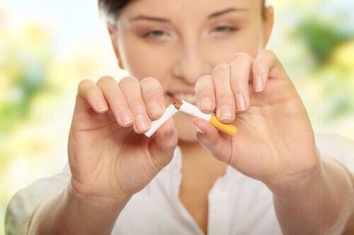 kvinna bryter av en cigarett