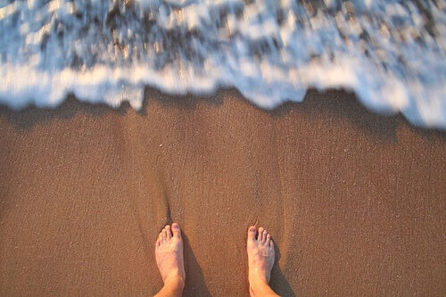 fötter på sandstrand