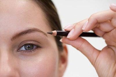 person målar eyeliner med brun penna