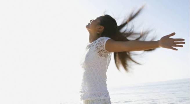 Glad kvinna med armarna öppna i vinden