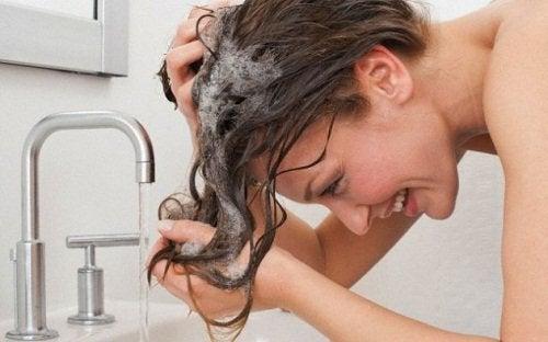 Kvinna schamponerar håret