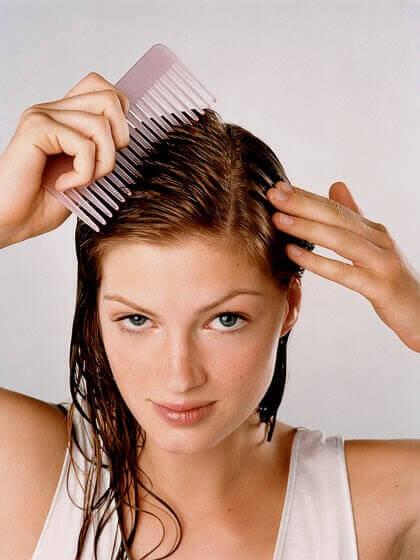 person kammar håret med en stortandad kam