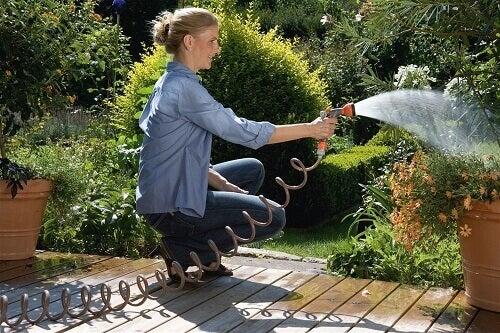 kvinna vattnar i trädgård