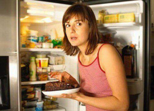 kvinna med begäret att äta ur kylen