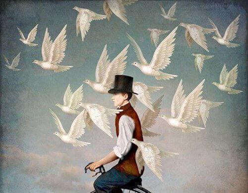 Man på cykel med vita fåglar runtomkring
