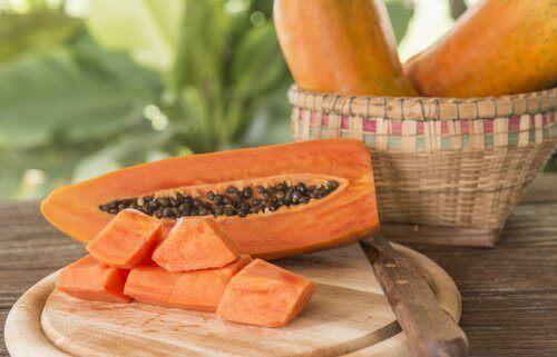 Papaya halva med kärnor och skuren papaya