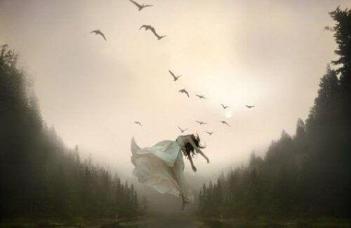 kvinna på äng med fåglar som flyger