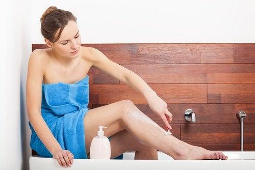 kvinna rakar benen i badkaret