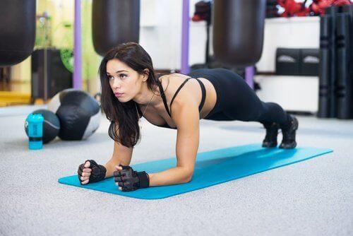 Kvinna gör plankan för att bli av med bukfett