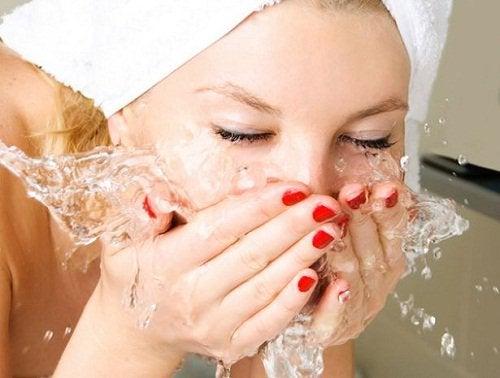 kvinna tvättar ansiktet med vatten