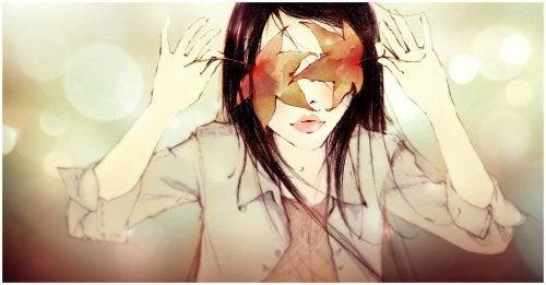 kvinna täcker över sina ögon med löv