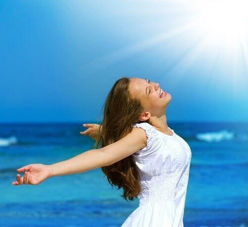 kvinna-badar-i-solljus-på-strand