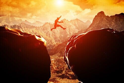 person hoppar över en klyfta i berg