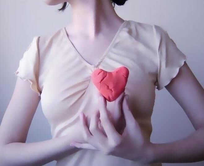 kvinna håller hjärta framför kroppen
