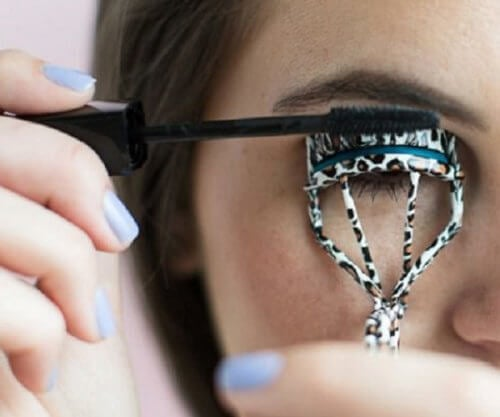 person som använder en ögonfransböjare