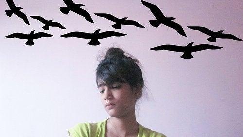 Fåglar kring kvinna