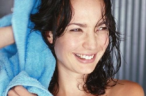 kvinna-torkar-nyduschat-glansigt-hår