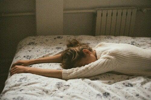 kvinna ledsen på en säng