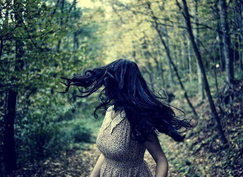 orädd kvinna ser sig om i skog