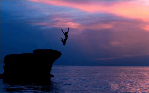 orädd kvinna hoppar från klippa i vattnet
