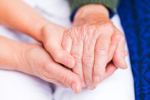 yngre och gammal håller händer