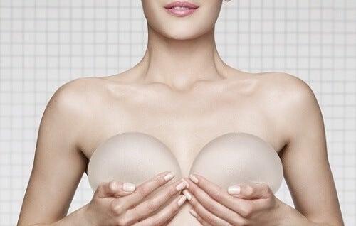 kvinna hållandes silikonimplantat framför brösten