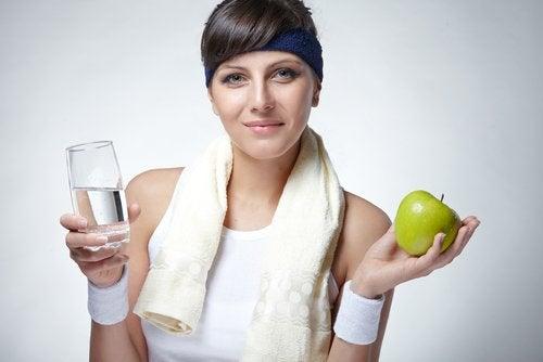 sportig kvinna med vatten och äpple i handen