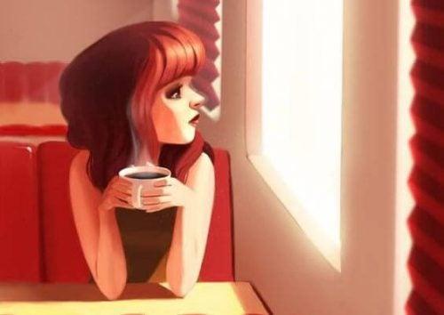 kvinna på kafe med en kopp kaffe i handen