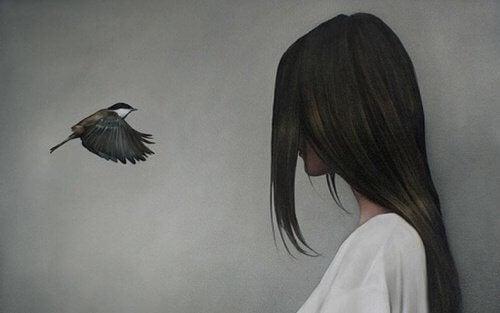 långhårig person tittar på en fågel