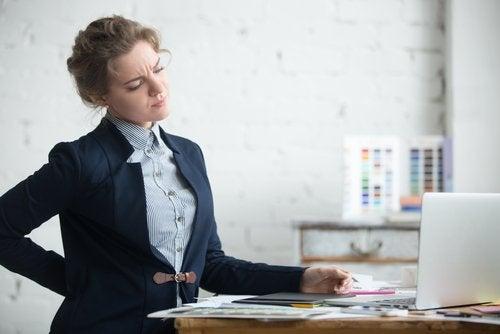 kvinna med ryggont vid dator