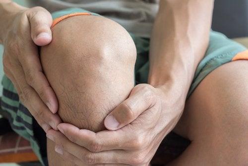 person som håller om sitt knä