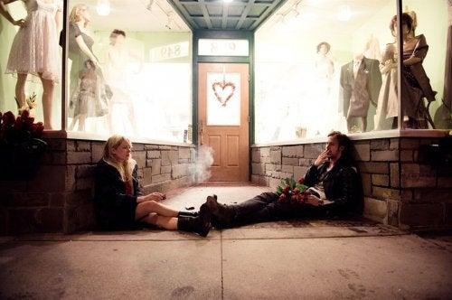 par som sitter utanför affär och röker