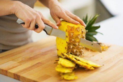 person tar bort skal på ananas med kniv
