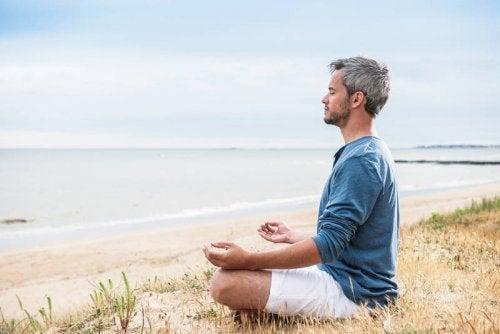 man som mediterar vid havet