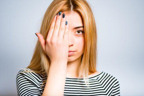 kvinna som håller för ena ögat med handen