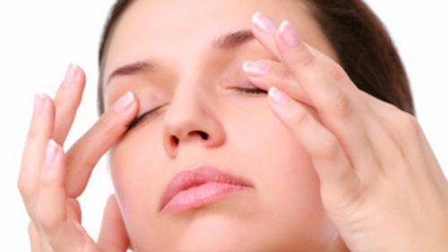 kvinna som masserar ögonlocken