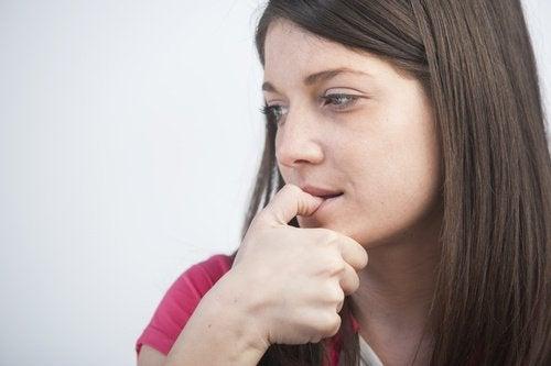 kvinna som biter på nagel