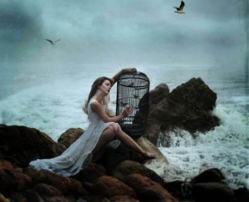 kvinna vid vatten med fågelbur i famn