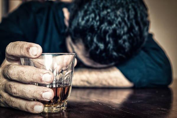person med huvudet på bordet och glas med alkohol i handen