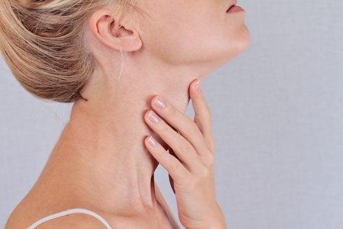kvinna rör sin hals