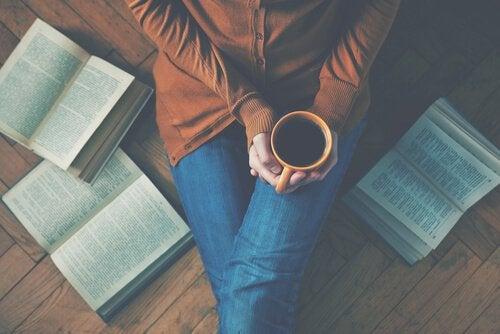 person med kopp kaffe bland uppslagna böcker