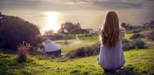 kvinna på kulle vid solnedgång