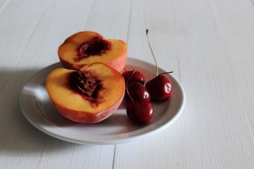 Tallrik med körsbär och persikor