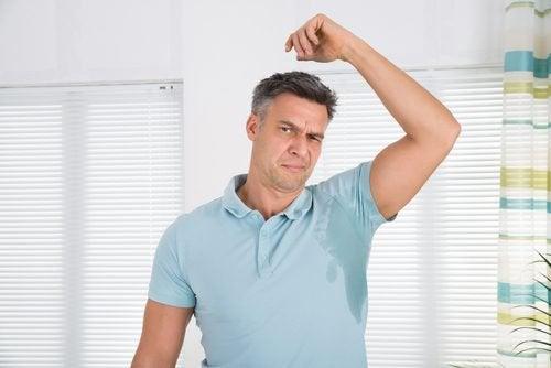 man grimaserar av svettfläck under armen