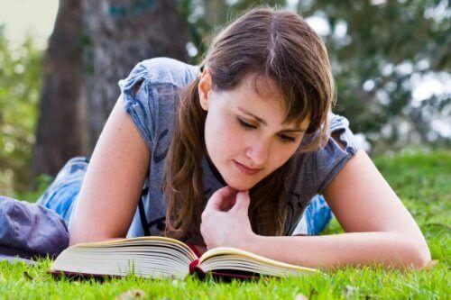 Kvinna läser i gräset