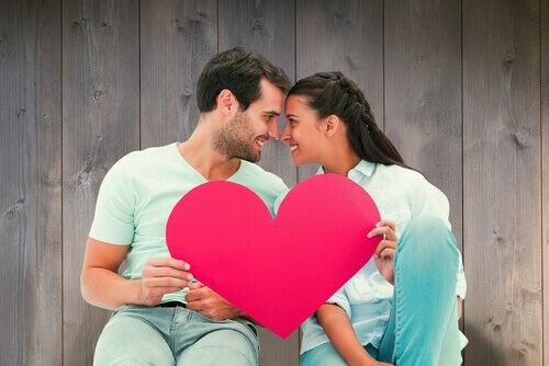 Par sitter med pappershjärta