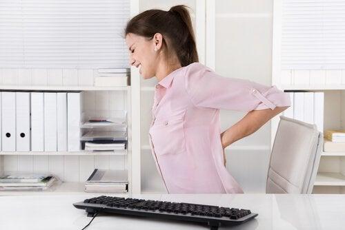kvinna har ont i ryggen