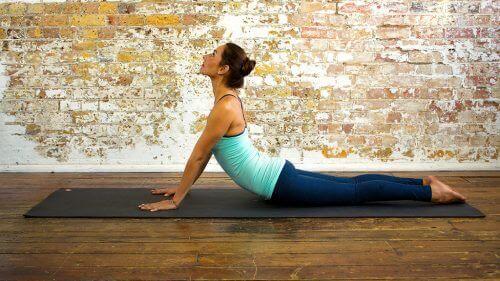 Kvinna stärker magen med kobrapositionen