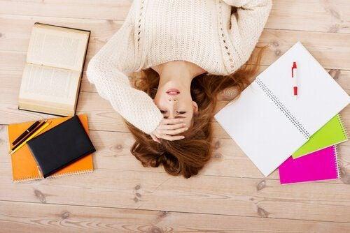 Kvinna ligger på golvet bland anteckningsblock