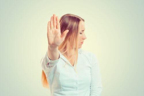 Kvinna håller upp handen framför sig